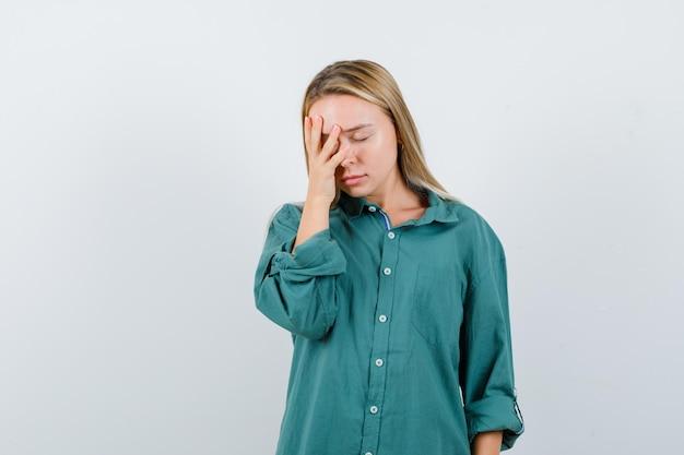 緑のシャツを着た若い女性が顔に手を保ち、疲れているように見える
