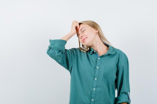 머리에 손을 유지하고 평화로운 찾고 녹색 셔츠에 젊은 아가씨
