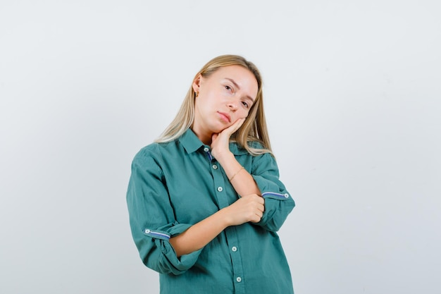 손바닥에 뺨을 기울고 예쁜 찾고 녹색 셔츠에 젊은 아가씨
