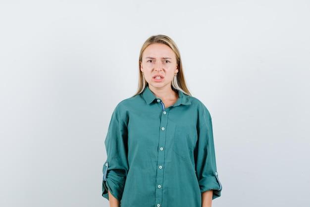 カメラを見て欲求不満に見える緑色のシャツを着た若い女性