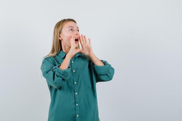 녹색 셔츠에 젊은 아가씨는 소리를 지르거나 뭔가를 발표하고 흥분된 찾고