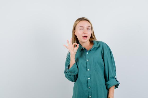 大丈夫なジェスチャーを示し、自信を持って見える緑色のシャツの若い女性