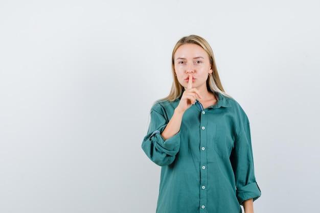 침묵 제스처를 보여주는 자신감을 찾고 녹색 셔츠에 젊은 아가씨