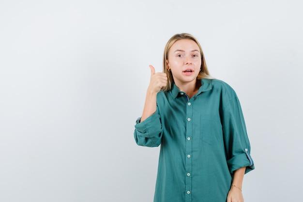 親指を立てて自信を持って見える緑色のシャツを着た若い女性