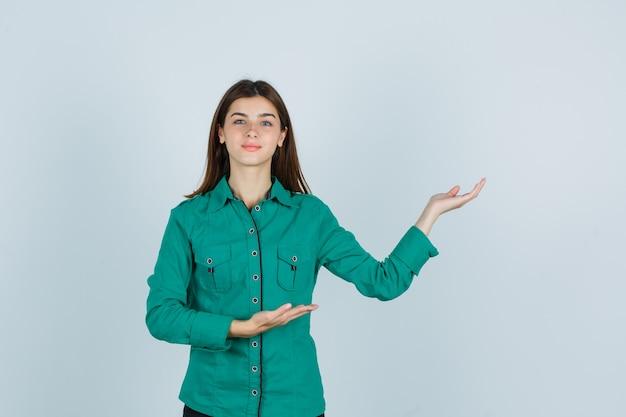 緑のシャツを着た若い女性は、歓迎のジェスチャーを示し、自信を持って、正面図を示しています。