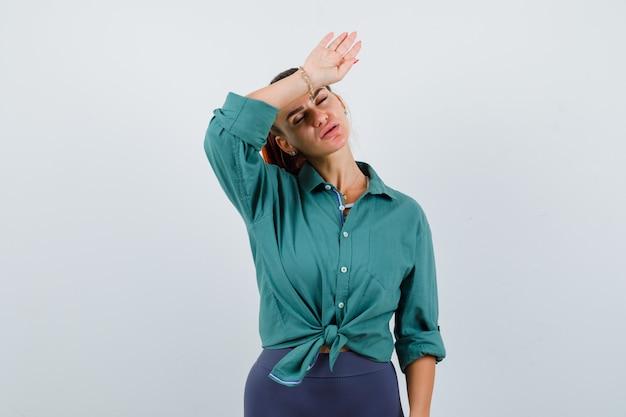 두통으로 고통받고 피곤해 보이는 녹색 셔츠를 입은 젊은 여성, 전면 보기.