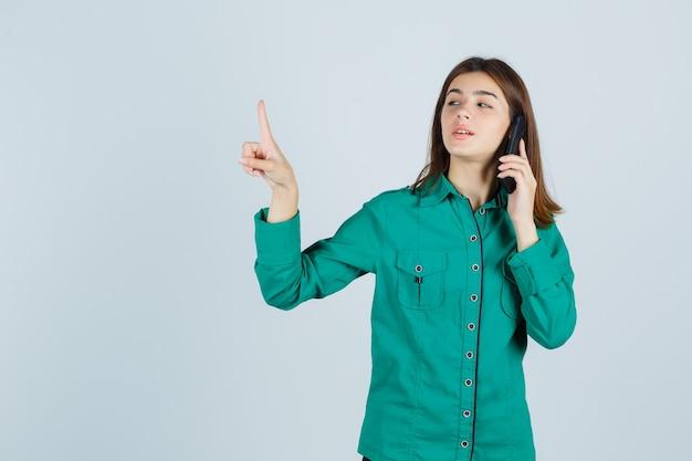 緑のシャツを着た若い女性が携帯電話で話し、細かいジェスチャーを保持し、自信を持って、正面図を示しています。