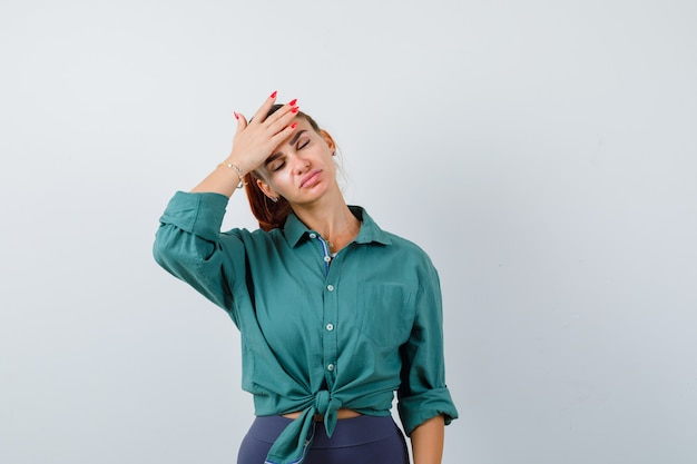 額に手があり、疲れ果てているように見える緑色のシャツを着た若い女性、正面図。