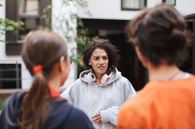 大学の中庭で時間を過ごしながら立って学生と話しているヘッドフォンの若い女性