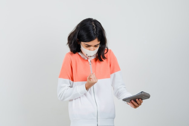 パーカーの若い女性、フェイスマスクの計算と集中して見える