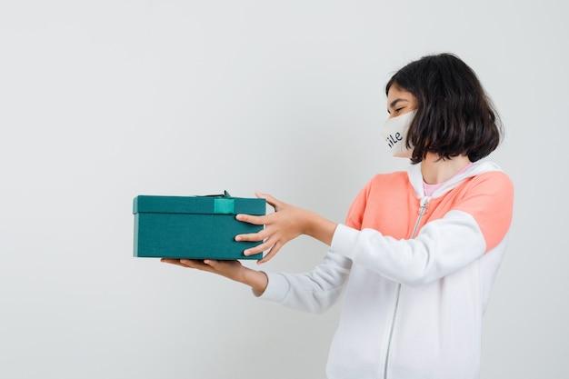 Молодая дама в толстовке с капюшоном, маска для лица держит подарочную коробку и выглядит счастливой.