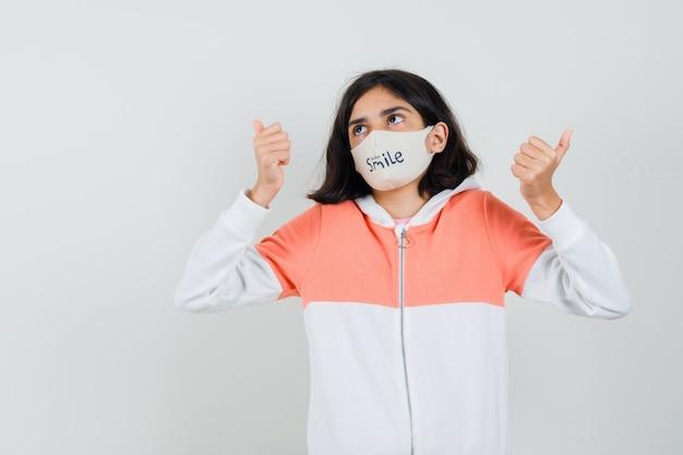 パーカーの若い女性、さまざまな側面を指し、混乱しているように見えるフェイスマスク