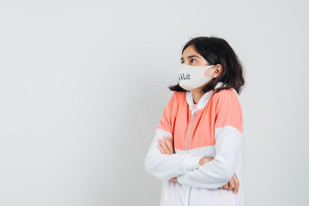 パーカーの若い女性、腕を組んで誰かと話しているフェイスマスク