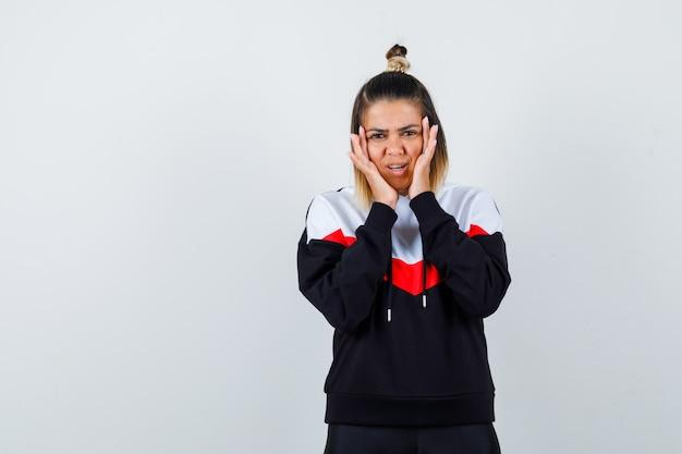頬に手をつないで、集中して見えるパーカーセーターの若い女性