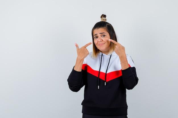 그녀의 뺨을 가리키고 예쁜 찾고 까마귀 스웨터에 젊은 여자