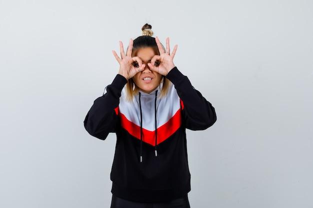 Молодая дама в свитере с капюшоном показывает жест в очках и выглядит удивленно