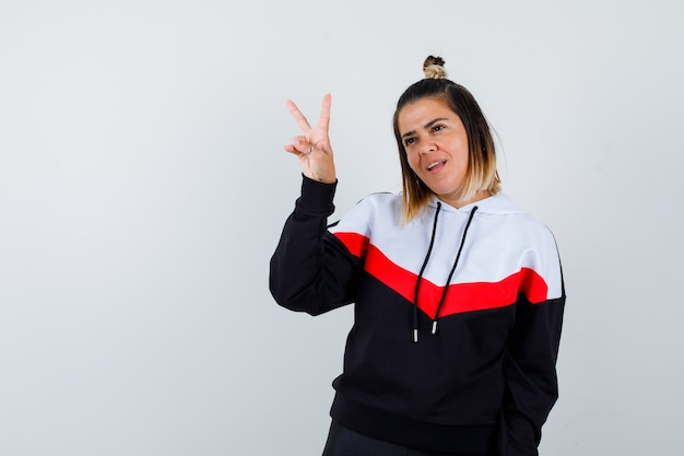 까마귀 스웨터를 입은 젊은 여성이 승리 기호를 표시하고 쾌활해 보입니다.