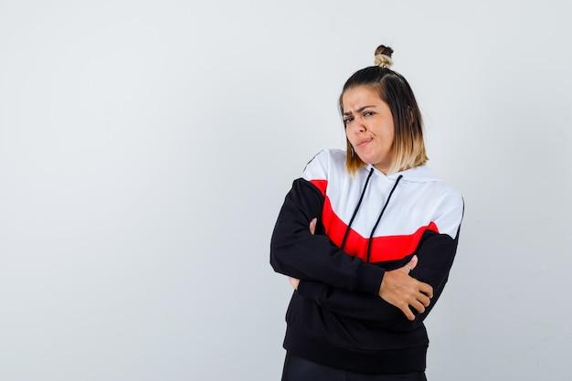 腕を組んで立って真剣に見えるパーカーセーターの若い女性