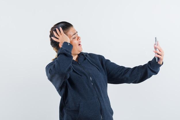 젊은 숙녀 재킷 제작 영상 통화 및 루킹 집중