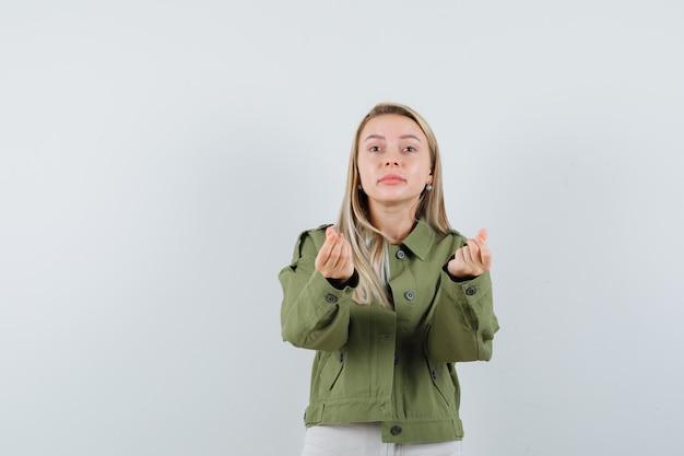 ジャケットの若い女性、お金のジェスチャーをしているズボン、正面図。