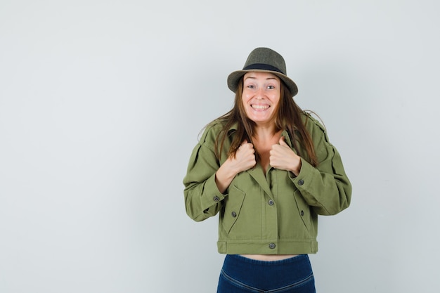 彼女の襟を保持し、陽気に見えるジャケットパンツ帽子の若い女性