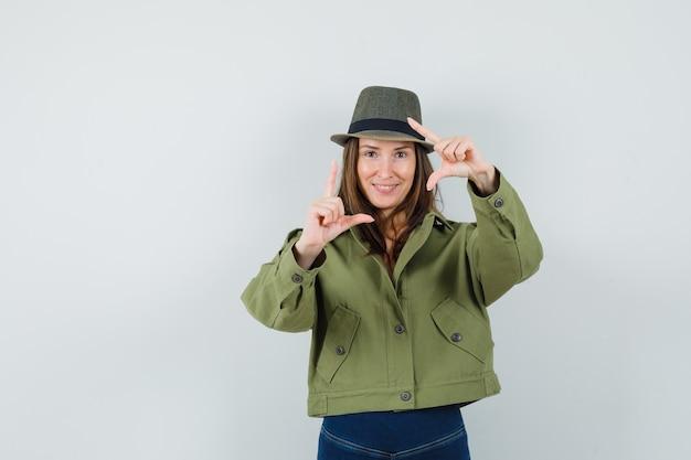 フレームジェスチャーを作成し、陽気に見えるジャケットパンツ帽子の若い女性