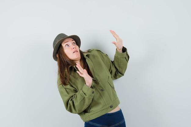 ジャケットパンツの帽子をかぶった若い女性は、身を守るために手を上げて怖がっています