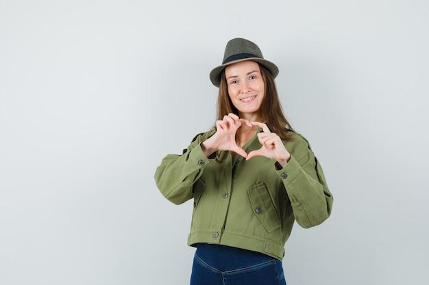 Молодая дама в шляпе с пиджаком и брюками показывает жест сердца и выглядит весело