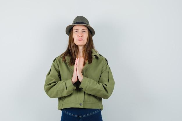 ナマステのジェスチャーを示し、悲しそうに見えるジャケットパンツ帽子の若い女性