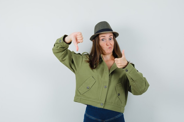 上下に親指を示し、躊躇しているジャケットパンツ帽子の若い女性