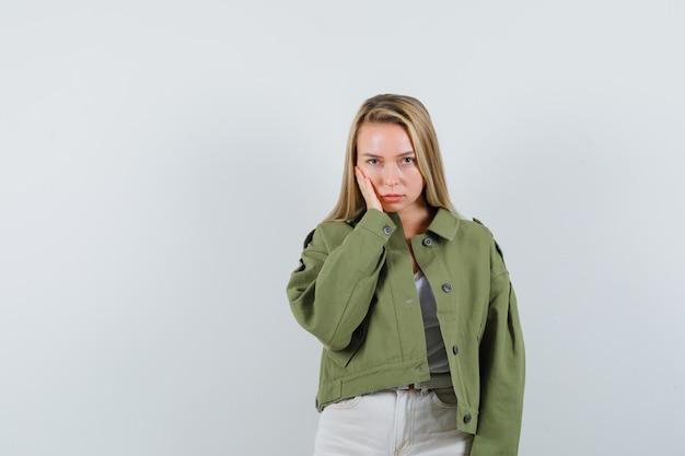 ジャケットを着た若い女性、頬に手をつないで悲しそうなズボン、正面図。