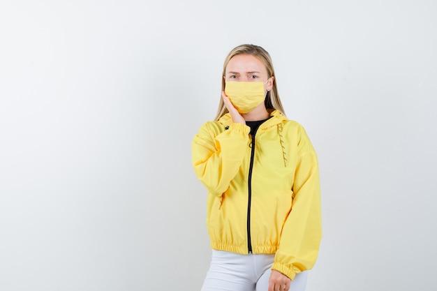 ジャケット、ズボン、歯痛に苦しんで悲しそうなマスク、正面図の若い女性。
