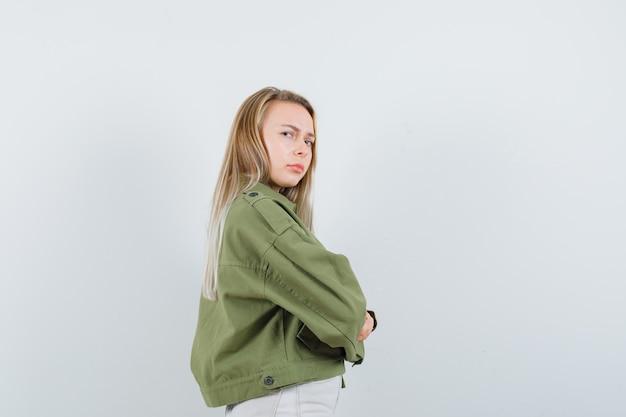Молодая дама в куртке, штанах стоит со скрещенными руками и выглядит сомнительно.