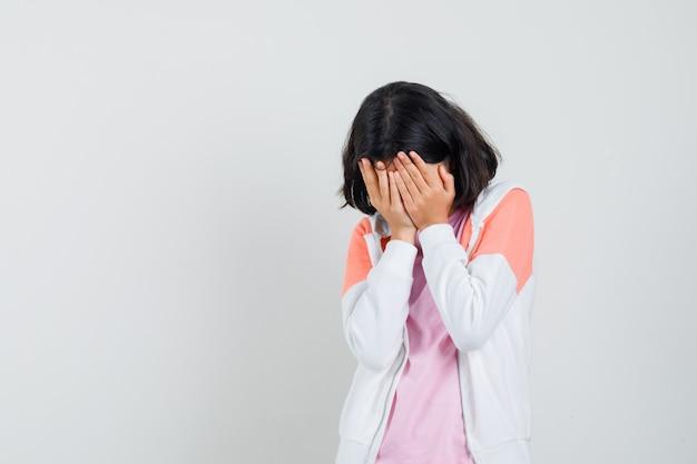 ジャケットを着た若い女性、彼女の顔に手をつないで悲しそうに見えるピンクのシャツ