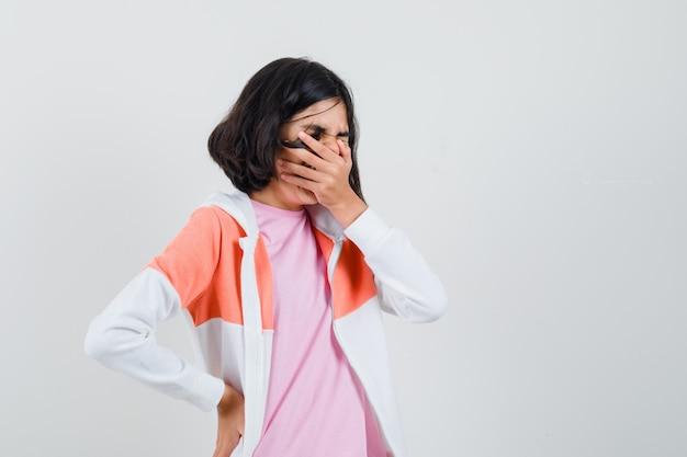 ジャケットの若い女性、くしゃみをしながら彼女の口に手をつないでピンクのシャツ
