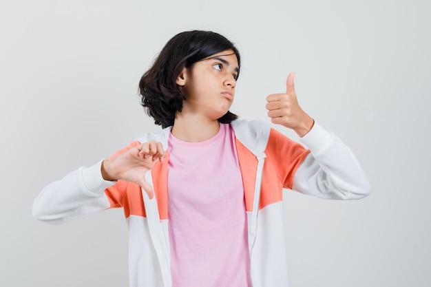 ジャケットの若い女性、親指を上下に見せて混乱しているピンクのシャツ