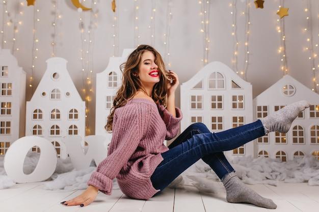紫のニットセーターを着たお嬢様が心から笑っています。白い段ボールの家に対して床にポーズをとるジーンズの女の子の全身写真