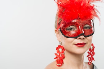 Young lady in mask with red feathers and earrings