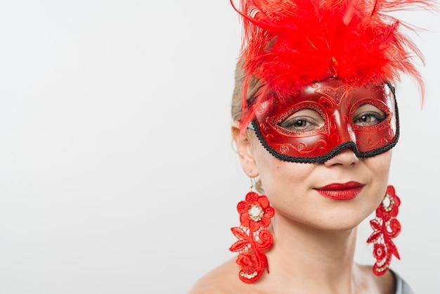붉은 깃털과 귀걸이와 마스크에 젊은 아가씨