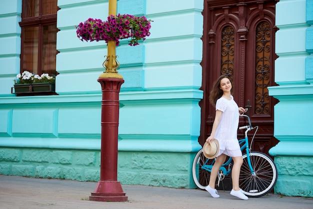 빈티지 문 배경에 복고풍 자전거와 함께 오래 된 도시에서 젊은 아가씨