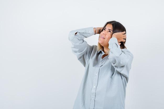 耳に手をつないで、焦点を合わせて見ている特大のシャツを着た若い女性、正面図。