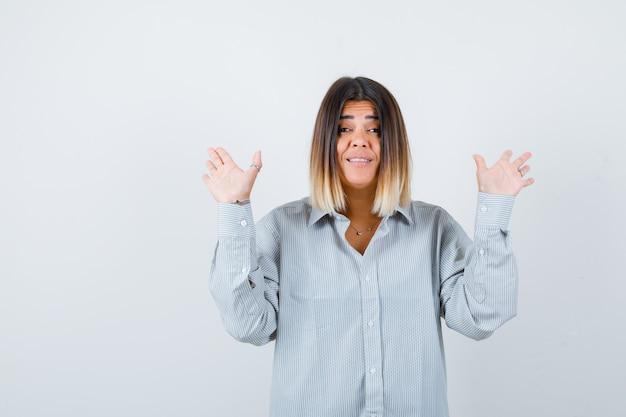 Молодая дама в рубашке негабаритных поднимает руки, показывая ладони и выглядит радостным, вид спереди.