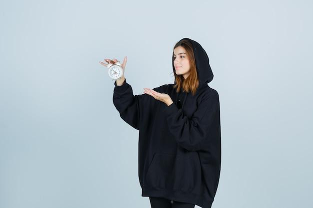 Девушка в огромной толстовке с капюшоном, в штанах держит будильник, притворяется, будто что-то показывает, и выглядит позитивно, вид спереди.