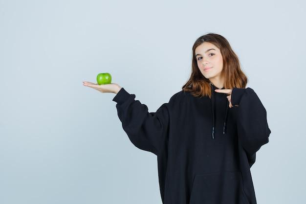 Молодая леди в огромной толстовке с капюшоном, в штанах держит яблоко, указывая на левую сторону и выглядит радостным, вид спереди.