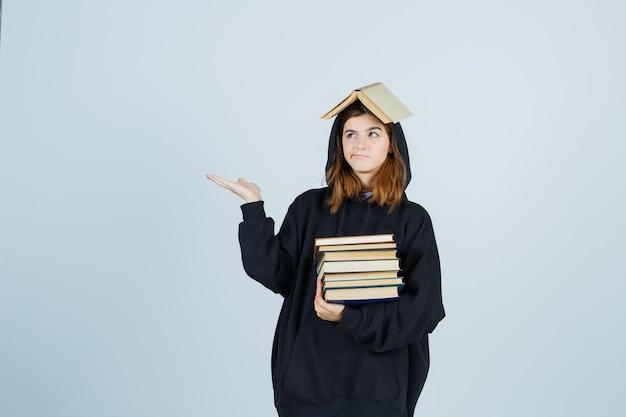 Молодая дама в огромной толстовке с капюшоном, в штанах держит книгу над головой, как крышу, с книгами и задумчиво выглядит, вид спереди.