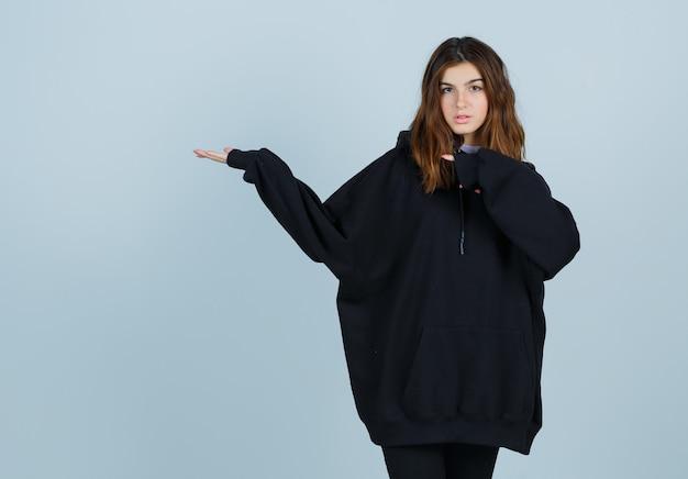 特大のパーカーを着た若い女性、彼女の手を指して自信を持って見えるパンツ、正面図。