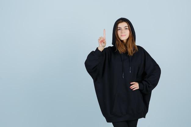 特大のパーカーを着た若い女性、上を向いて自信を持って見えるパンツ、正面図。