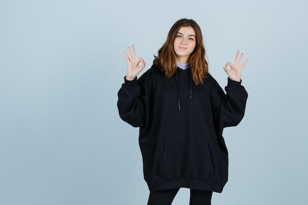 Молодая дама в огромной толстовке с капюшоном, штанах показывает жест «ок» и выглядит блаженно, вид спереди.