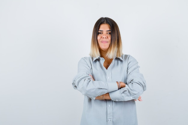 腕を組んで立って自信を持って見える特大のシャツを着た若い女性、正面図。