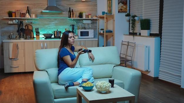 ソファに座ってリビングルームでテレビを見ているパジャマの若い女性。退屈な、夜遅くに一人で家にいる女性は、テレビのチャンネルを変更するリモコンを持って快適なソファに横たわってテレビを見てリラックスしています。 Premium写真